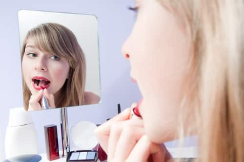 Image result for girl applying lipstick in mirror