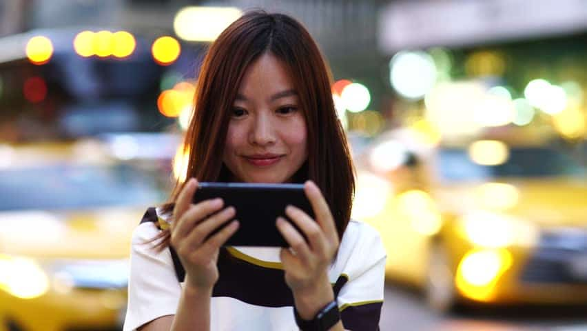 Image result for woman playing game on smartphone