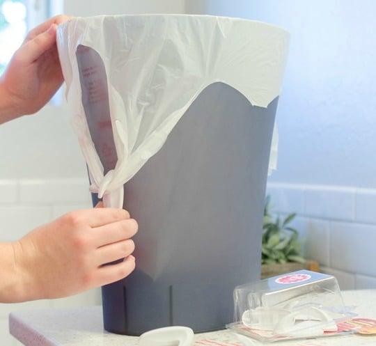 1. Kehilangan Tutup Tempat Sampah? Rekatkan Gantungan Serba Guna di Bagian Tengah dan Kaitkan dengan Kantong Plastik
