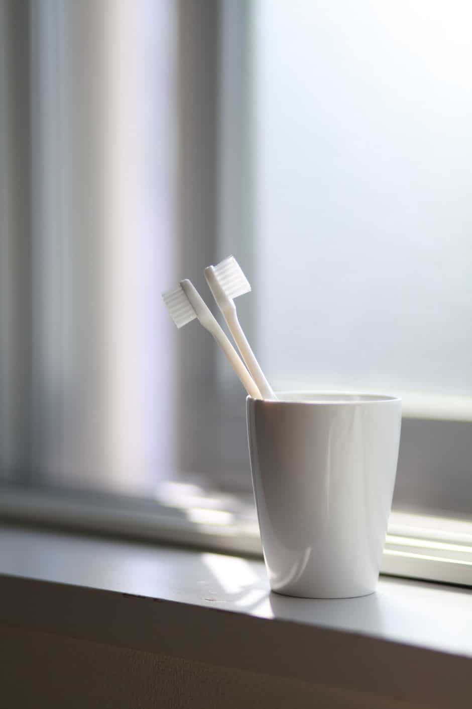 Two White Toothbrush Inside the White Ceramic Cup