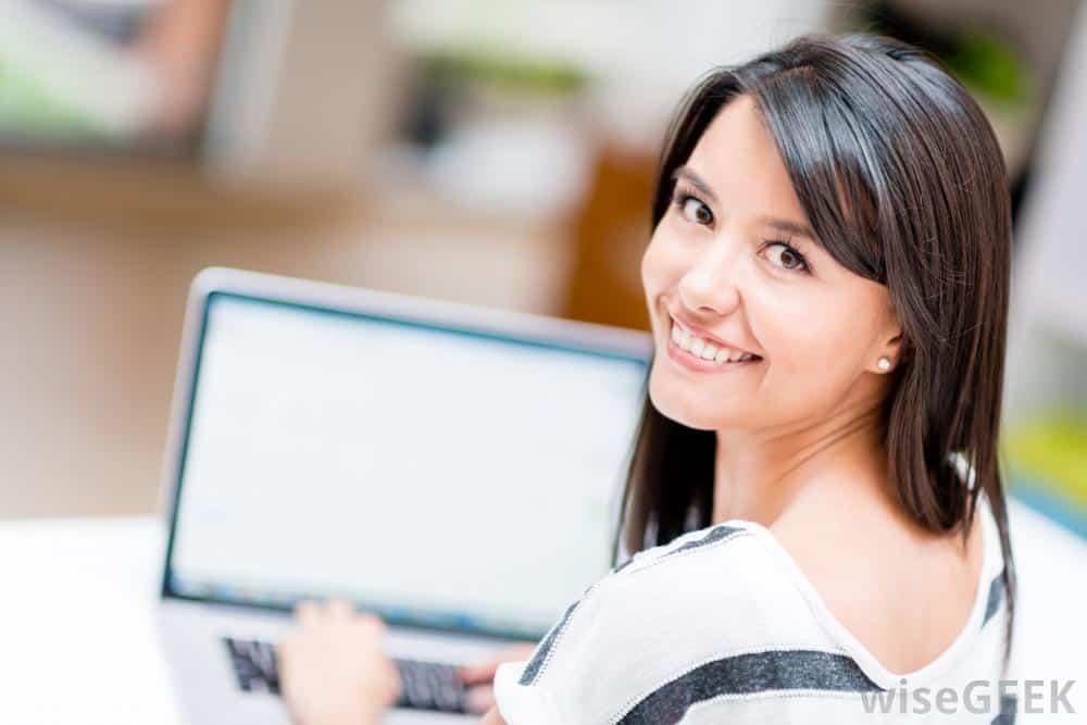 woman looking over shoulder at computer - Lagi Ujian? Coba 5 Tips yang Dijamin Bikin Pelajaran Lebih Mudah Diingat