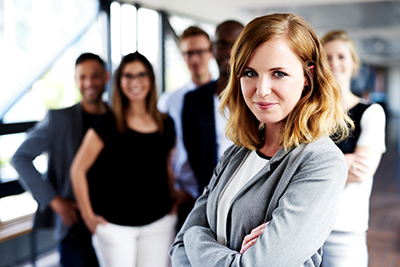 Female executive gazing at camera with arms crossed