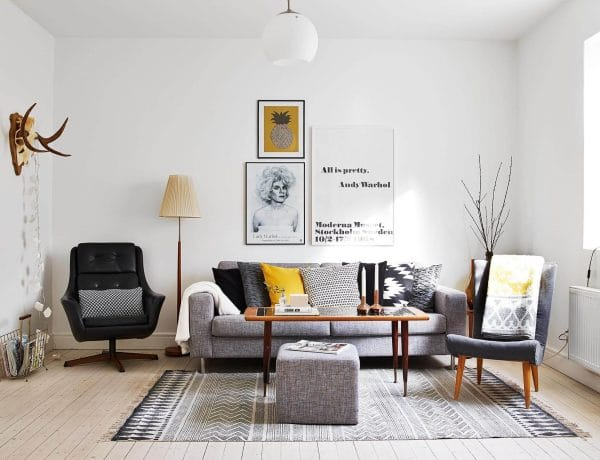 cool small scandinavian living room with grey sofa and black chair as well as ethnic pattern area rug and wood coffee table 600x460 - 4 Trik Mudah Bikin Ruangan Sempit Tampak Lebih Luas